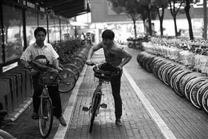 9月18日晚高峰时段,两位市民在天一广场旁的公共自行车网点借车出行。