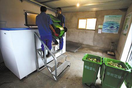 图为工人在向食物垃圾处理机内倒垃圾。