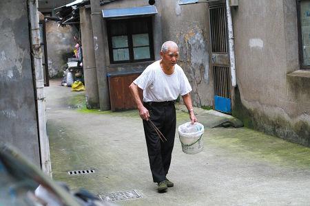 图为老人正在清除小巷路面垃圾。(李超 摄)
