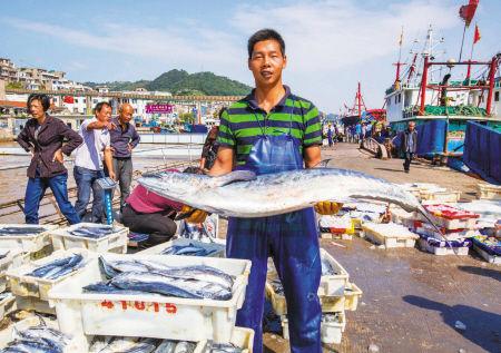 渔船的渔民在展示这次带回来的海鲜之一,一条重达27公斤的马鲛鱼。通讯员 蒋曼儒 摄