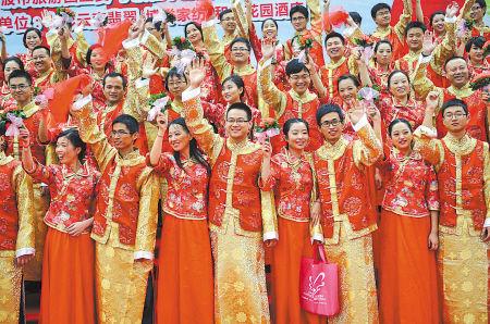 """三江情大红鹰玫瑰婚典现场,百对新人演绎现代版""""十里红妆""""。(丁安 摄)"""
