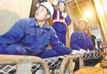 在东部新城宁波航运中心内,宁波电力配网公司施工人员正在用绞模机把碗口粗的主电缆通上高楼。(胡建华 王幕宾 谭智 摄)