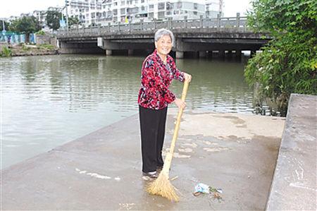 图为正在打扫河埠头的丁阿婆。