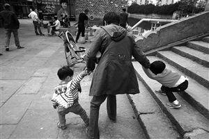 南塘老街,一位女士被两个小孩拉扯得进退不得