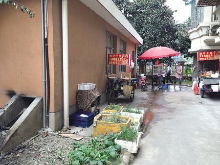 南裕小区配电房旁停放的烧烤车,左侧墙面黑色处为着火点。(王伊婧 摄)